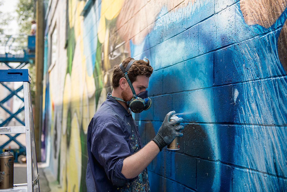 Artist painting a wall during the Nelson International Mural Festival
